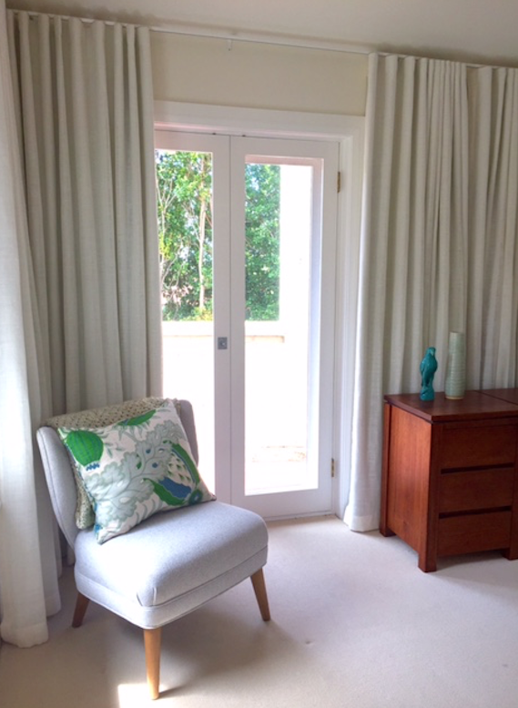 The AFTER shot:  Beautiful and simple - this bedroom was transformed with cream linen curtains and a punch of rich green and blue and soft grey.